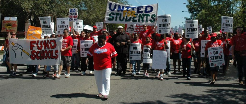 """CTU members march holding signs with """"United for students."""""""